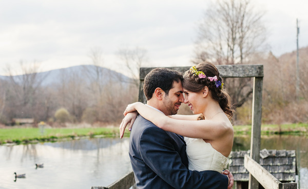 Couple embrace at duck pond in early spring with Eagle Mountain in the background