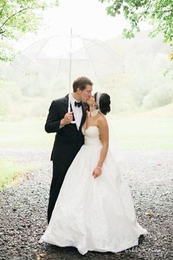 Wedding couple kissing under umbrellain the rain