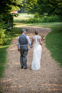 August wedding- couple walking along field path