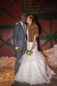 Couple kissing in the snow outside of the Spruce Wedding Barn