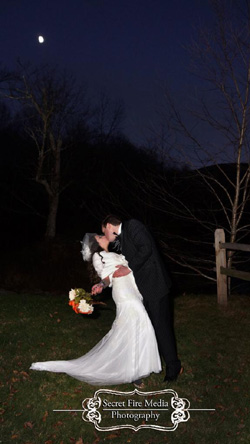 Dramatic wedding kiss under the Halloween moon