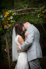 August wedding- couple kissing under canopy of flowers