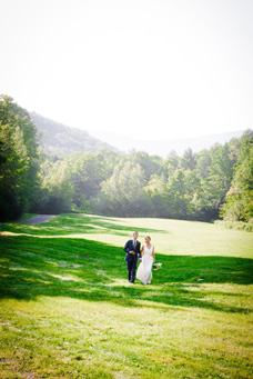 Wedding couple holding hands in field
