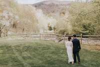 Wedding couple walk along field fence, with mountain view
